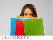 Купить «teenage student girl hiding behind notebooks», фото № 30529516, снято 29 января 2019 г. (c) Syda Productions / Фотобанк Лори