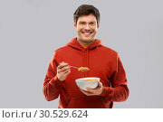 smiling young man in red hoodie eating cereals. Стоковое фото, фотограф Syda Productions / Фотобанк Лори