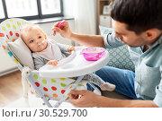 Купить «father feeding happy baby in highchair at home», фото № 30529700, снято 25 августа 2018 г. (c) Syda Productions / Фотобанк Лори