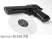 Target with holes and gun. Стоковое фото, фотограф Tryapitsyn Sergiy / Фотобанк Лори