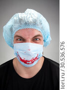 Mad mental sick surgeon with blood smile on mask. Стоковое фото, фотограф Tryapitsyn Sergiy / Фотобанк Лори