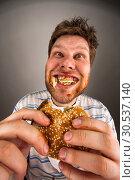 Купить «Man chewing hamburger», фото № 30537140, снято 1 мая 2011 г. (c) Tryapitsyn Sergiy / Фотобанк Лори
