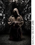 Praying monk in dark temple corridor. Стоковое фото, фотограф Tryapitsyn Sergiy / Фотобанк Лори