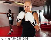 Купить «Potrait of man boxer who is training in gym», фото № 30538304, снято 28 января 2019 г. (c) Яков Филимонов / Фотобанк Лори