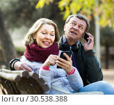 Купить «Mature couple with smartphones outdoors», фото № 30538388, снято 23 августа 2019 г. (c) Яков Филимонов / Фотобанк Лори