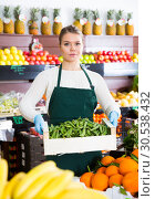 Купить «Salesgirl offering green beans», фото № 30538432, снято 31 января 2019 г. (c) Яков Филимонов / Фотобанк Лори