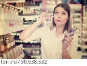 Купить «Young woman smelling perfume testers in cosmetics shop», фото № 30538532, снято 31 января 2018 г. (c) Яков Филимонов / Фотобанк Лори