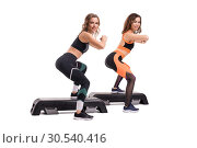 Купить «Two slim women in sportswear doing fitness view», фото № 30540416, снято 17 октября 2018 г. (c) Гурьянов Андрей / Фотобанк Лори