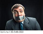 Купить «Man with mouth covered by masking tape», фото № 30548060, снято 21 апреля 2014 г. (c) Tryapitsyn Sergiy / Фотобанк Лори