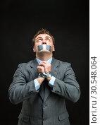 Купить «Man with mouth covered by masking tape», фото № 30548064, снято 21 апреля 2014 г. (c) Tryapitsyn Sergiy / Фотобанк Лори