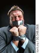 Купить «Man with mouth covered by masking tape», фото № 30548068, снято 21 апреля 2014 г. (c) Tryapitsyn Sergiy / Фотобанк Лори