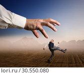 Businessman runs from a big arm. Стоковое фото, фотограф Tryapitsyn Sergiy / Фотобанк Лори