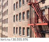 Купить «Closeup of brick building with fire ladders.», фото № 30555976, снято 9 июня 2016 г. (c) Tryapitsyn Sergiy / Фотобанк Лори