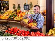 Купить «Seller suggests to buy ripe fruits.», фото № 30562992, снято 26 октября 2016 г. (c) Tryapitsyn Sergiy / Фотобанк Лори
