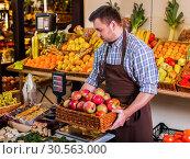 Купить «Seller holding a box with apples on weights.», фото № 30563000, снято 26 октября 2016 г. (c) Tryapitsyn Sergiy / Фотобанк Лори