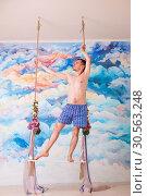 Купить «Amorous man in underpants stay on wooden swing», фото № 30563248, снято 5 ноября 2016 г. (c) Tryapitsyn Sergiy / Фотобанк Лори