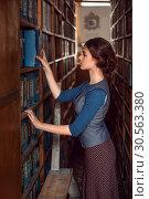 Купить «Woman taking a book from bookshelf.», фото № 30563380, снято 20 ноября 2016 г. (c) Tryapitsyn Sergiy / Фотобанк Лори