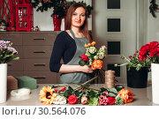 Купить «Female florist working with flowers», фото № 30564076, снято 11 декабря 2016 г. (c) Tryapitsyn Sergiy / Фотобанк Лори