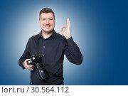 Professional photographer with camera shows ok. Стоковое фото, фотограф Tryapitsyn Sergiy / Фотобанк Лори