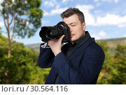 Photographer with photo camera takes the picture. Стоковое фото, фотограф Tryapitsyn Sergiy / Фотобанк Лори