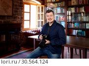 Photographer with digital camera sitting on chair. Стоковое фото, фотограф Tryapitsyn Sergiy / Фотобанк Лори