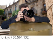 Photographer takes a picture leaning on barrel. Стоковое фото, фотограф Tryapitsyn Sergiy / Фотобанк Лори