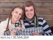 Happy lovely couple wrapped in plaid. Стоковое фото, фотограф Tryapitsyn Sergiy / Фотобанк Лори