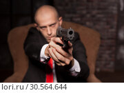 Купить «Bald killer in suit and red tie aims a pistol», фото № 30564644, снято 19 января 2017 г. (c) Tryapitsyn Sergiy / Фотобанк Лори