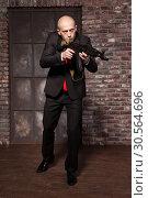 Купить «Assassin in suit and red tie holding machine gun», фото № 30564696, снято 19 января 2017 г. (c) Tryapitsyn Sergiy / Фотобанк Лори