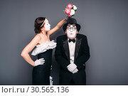 Купить «Comedy actor and actress poses with flower bouquet», фото № 30565136, снято 12 февраля 2017 г. (c) Tryapitsyn Sergiy / Фотобанк Лори
