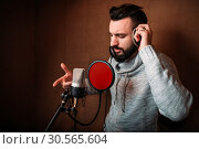 Купить «Male singer recording a song in music studio», фото № 30565604, снято 21 февраля 2017 г. (c) Tryapitsyn Sergiy / Фотобанк Лори