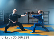 Купить «Male and female wushu fighters exercises indoor», фото № 30566828, снято 26 мая 2017 г. (c) Tryapitsyn Sergiy / Фотобанк Лори