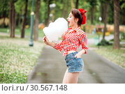 Sexy pinup girl with sweet cotton candy on stick. Стоковое фото, фотограф Tryapitsyn Sergiy / Фотобанк Лори