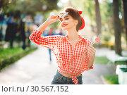Sexy pin up girl with lollipop walks in a park. Стоковое фото, фотограф Tryapitsyn Sergiy / Фотобанк Лори