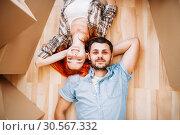 Купить «Couple lies on the floor, top view, new house», фото № 30567332, снято 29 июня 2017 г. (c) Tryapitsyn Sergiy / Фотобанк Лори