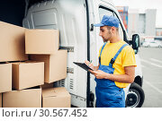 Cargo delivery, male courier with box in hand. Стоковое фото, фотограф Tryapitsyn Sergiy / Фотобанк Лори