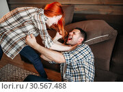 Купить «Angry wife beats her husband, domestic violence», фото № 30567488, снято 19 июля 2017 г. (c) Tryapitsyn Sergiy / Фотобанк Лори