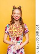Funny teenage girl holdss big lollipop. Стоковое фото, фотограф Tryapitsyn Sergiy / Фотобанк Лори