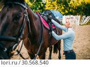 Купить «Female rider preparing a horse saddle,», фото № 30568540, снято 17 сентября 2017 г. (c) Tryapitsyn Sergiy / Фотобанк Лори