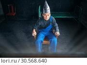 Scared man in aluminum foil hat sits in chair. Стоковое фото, фотограф Tryapitsyn Sergiy / Фотобанк Лори