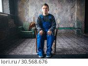 Купить «Crasy man sitting in the chair, psycho patient», фото № 30568676, снято 1 октября 2017 г. (c) Tryapitsyn Sergiy / Фотобанк Лори