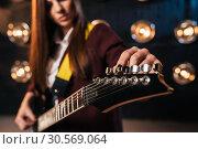 Купить «Female rock guitarist in suit tunes the guitar», фото № 30569064, снято 10 ноября 2017 г. (c) Tryapitsyn Sergiy / Фотобанк Лори