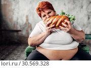 Fat woman sits in chair and eats sandwich, bulimic. Стоковое фото, фотограф Tryapitsyn Sergiy / Фотобанк Лори