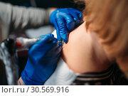 Купить «Female tattooer makes tattoo by machine», фото № 30569916, снято 22 декабря 2017 г. (c) Tryapitsyn Sergiy / Фотобанк Лори