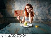 Купить «Woman holds help sign against plate with apple», фото № 30570064, снято 10 января 2018 г. (c) Tryapitsyn Sergiy / Фотобанк Лори