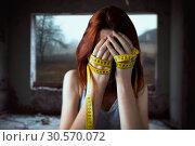 Купить «Woman covers face, hands tied with measuring tape», фото № 30570072, снято 10 января 2018 г. (c) Tryapitsyn Sergiy / Фотобанк Лори