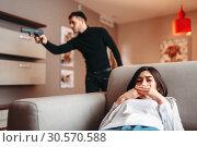 Купить «Woman hiding against killer with gun», фото № 30570588, снято 11 февраля 2018 г. (c) Tryapitsyn Sergiy / Фотобанк Лори
