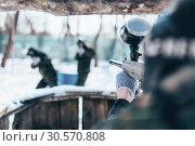 Купить «Paintball player shooting at the enemy team», фото № 30570808, снято 25 февраля 2018 г. (c) Tryapitsyn Sergiy / Фотобанк Лори