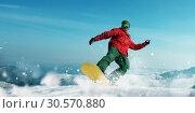 Купить «Snowboarder makes a jump, sportsman in action», фото № 30570880, снято 27 мая 2020 г. (c) Tryapitsyn Sergiy / Фотобанк Лори