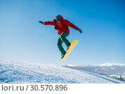 Snowboarder makes a jump on speed slope. Стоковое фото, фотограф Tryapitsyn Sergiy / Фотобанк Лори